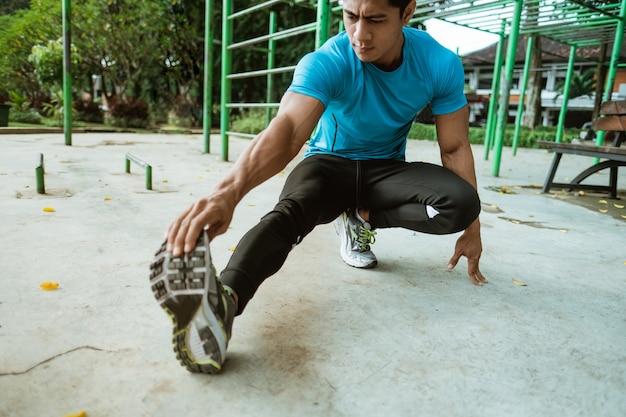 スポーツウェアの男性が公園でのトレーニングの前に脚のストレッチを行います