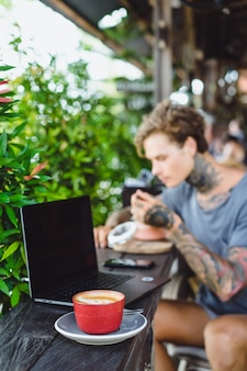 A man in tattoos breakfasts in an outdoor cafe, works on a laptop, drinks coffee.