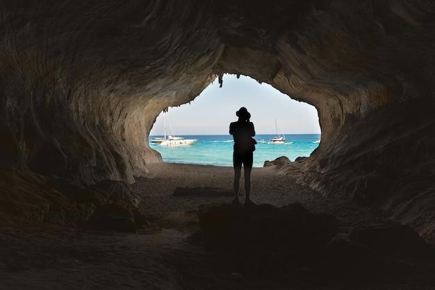 큰 동굴에 있는 남자, 내부에서 보기. 지중해 연안, 사르데냐, 이탈리아입니다.