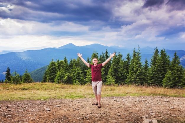 空の腕に向かって持ち上げられた山の男。男は山の中で自然の中で幸せを感じます