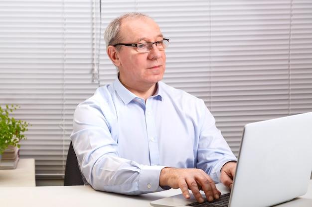 Мужчина в офисе в очках за компьютером печатает на клавиатуре.