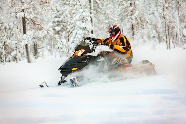 Мужчина в костюме гонщика в желто-черном комбинезоне и красно-черном шлеме едет на снегоходе на большой скорости по глубокому снегу на фоне заснеженного леса.