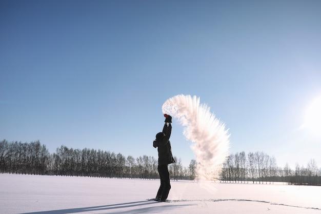 겨울 거리의 한 남자. 그 남자는 겨울 길을 걷습니다. 다운 재킷을 입은 청년이 눈 속에서 뛰어오르고 있습니다.