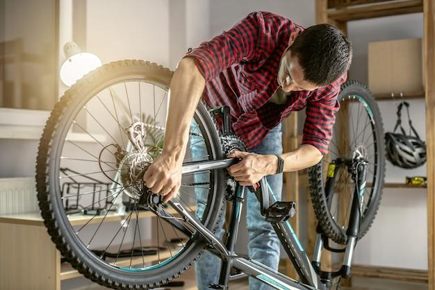 작업장에 있는 한 남자가 자전거를 분해하고 수리하고 있습니다. 새 시즌을 위한 유지 관리 및 준비의 개념
