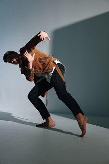 ズボンと茶色のコートを着た男がカーブを登る