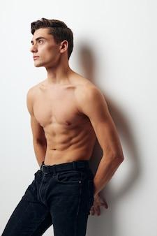 К стене прислонился мужчина в брюках с голым торсом. фото высокого качества
