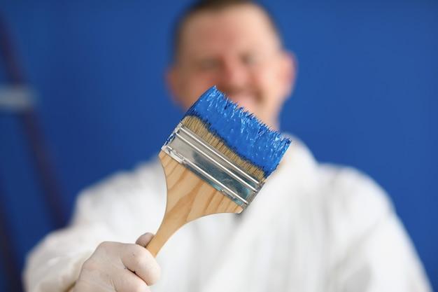 Мужчина в военной форме держит кисть с синей краской крупным планом. покраска стены в комнате. ремонт помещения