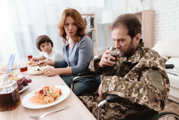 制服を着た男が台所のテーブルに座っています。