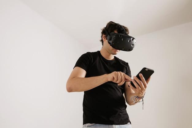 Vr 안경을 쓴 남자와 흰색 바탕에 스마트 폰 화면을 스 와이프하는 라벨이없는 검은 색 티셔츠
