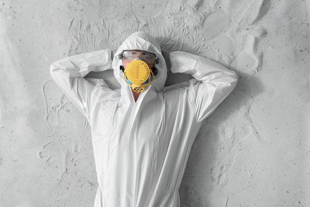 흰색 보호 유니폼, 인공 호흡기 및 플라스틱 투명 안경을 착용 한 사람.
