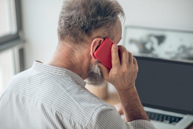 自宅で働く手にスマートフォンを持つ白いtシャツの男