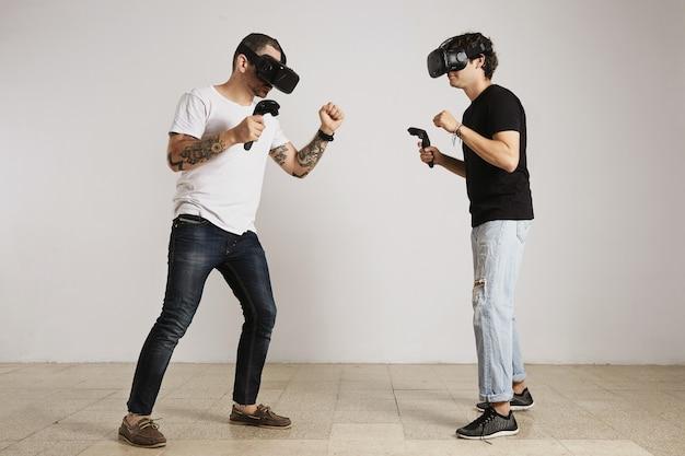 Мужчина в белой футболке без надписи с медведем и татуировками и мужчина в черной футболке без надписи в гарнитурах виртуальной реальности сражаются в комнате с белыми стенами.
