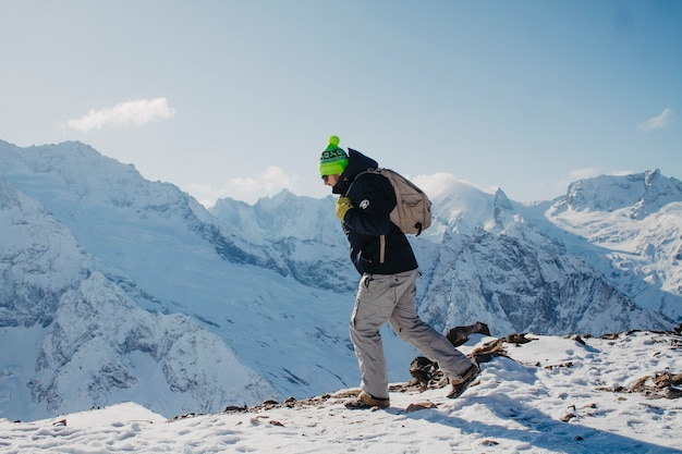겨울 옷을 입은 남자가 산을 올라갑니다.
