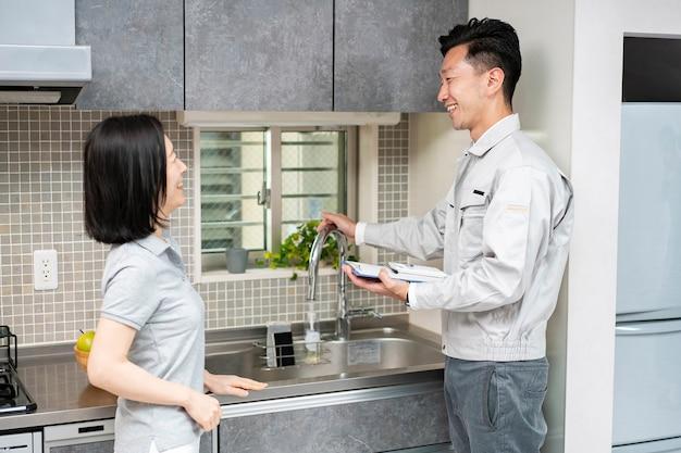 キッチンで女性に説明する作業服を着た男性