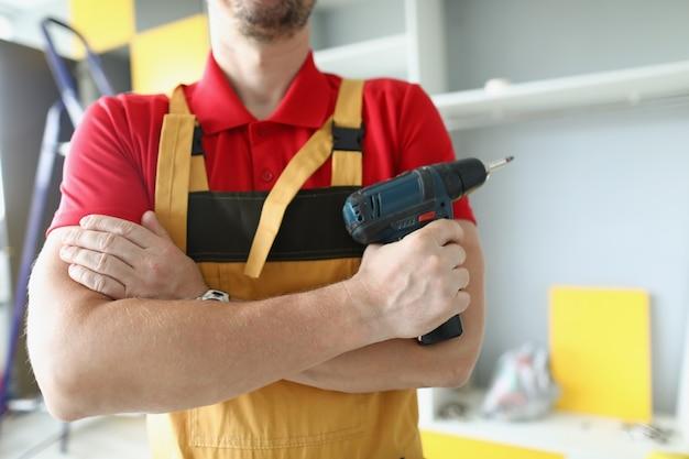 作業服を着た男性が腕を胸に組んでドライバーを持っている