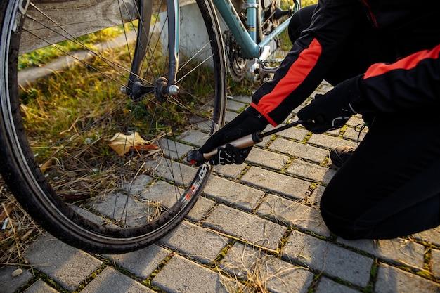 한 남자가 자전거 앞바퀴를 부풀립니다.