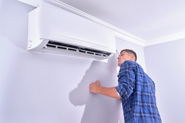 Мужчина осматривает кондиционер дома, проверяет, работает ли он