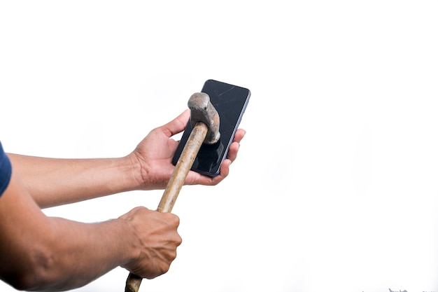 남자가 큰 망치로 스마트폰을 부수고 있다