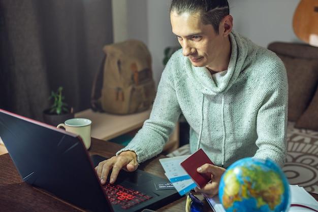 Мужчина покупает авиабилеты через интернет с помощью ноутбука в долгожданную поездку