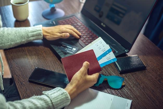 한 남자가 오랫동안 기다려온 여행을 위해 노트북을 사용하여 인터넷을 통해 항공권을 구매하고 있습니다.