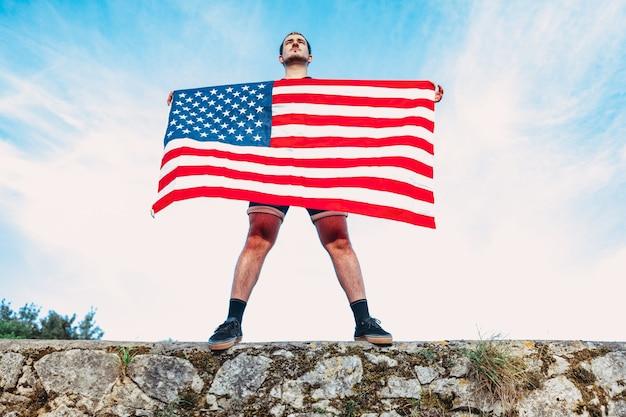 한 남자가 미국의 국기를 쥐고 있다. 애국심을 개념으로