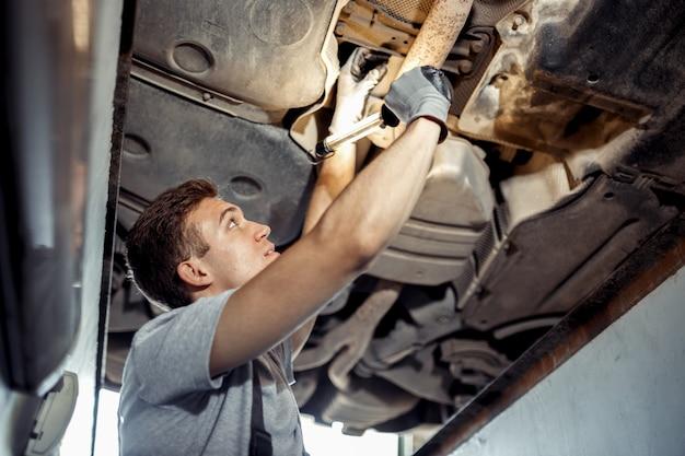 Мужчина проводит детальный осмотр поднятого автомобиля в автосервисе.
