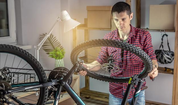 한 남자가 유지 보수를 위해 산악 자전거를 분해하고 있습니다. 새 시즌을 위한 자전거 고정 및 준비의 개념