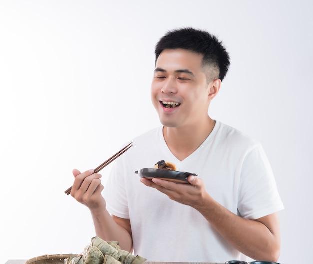 한 남자가 맛있는 종즈 (쌀 만두)를 먹고 용선 축제, 아시아 전통 음식, 흰색 배경에서 맛있게 느껴집니다.