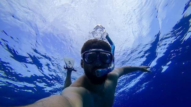 Мужчина занимается снорклингом, ныряет в глубины красного моря в маске и дыхательной трубке.