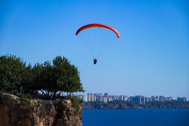 男は街のパノラマの崖の上の海の上のパラグライダーで飛んでいます
