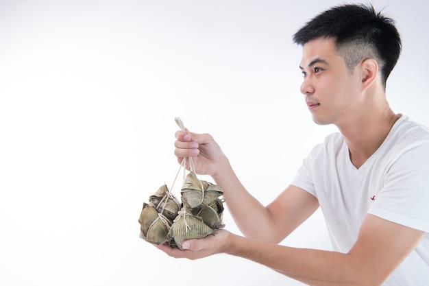 한 남자가 드래곤 보트 축제, 아시아 전통 음식, 흰색 배경에 선물이나 기념품으로 종지 또는 쌀 만두를 다른 사람에게주고 있습니다.