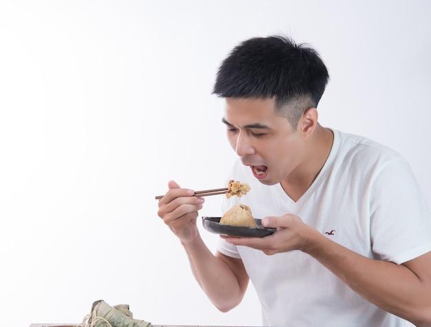 한 남자가 드래곤 보트 축제, 아시아 전통 음식, 흰색 배경에 맛있는 zongzi (쌀 만두)를 먹을 것입니다.