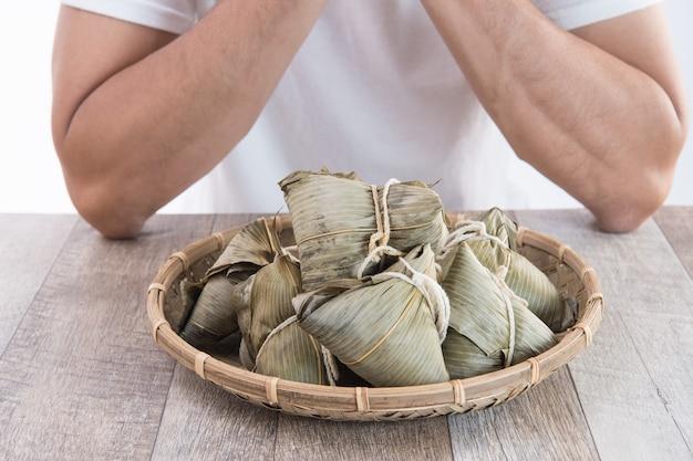 한 남자가 아시아 전통 음식 인 용선 축제에서 종지 또는 쌀 만두를 먹을 예정입니다.