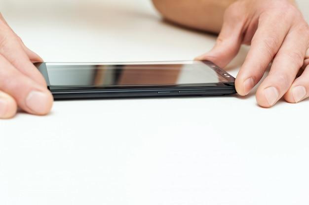 Мужчина держит защитное стекло для смартфона.