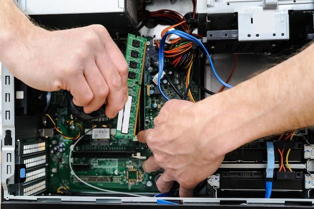 コンピュータをアップグレードするために、男性がramスロットを持っています。