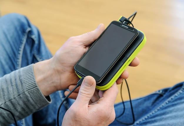 男はスマートフォンとパワーバンクを持っています。