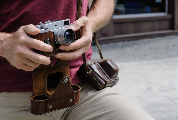 男はビンテージカメラを持っています。彼の片方の手はレンズをセットしています。