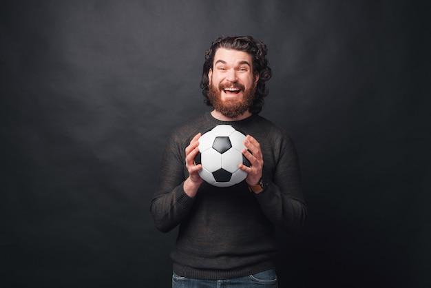 Мужчина держит возбужденный футбольный мяч возле черной стены