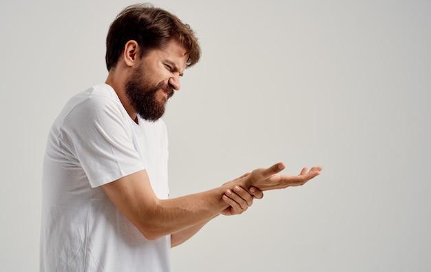 한 남자가 고통스러워하고 밝은 배경에서 손을 만집니다. 고품질 사진
