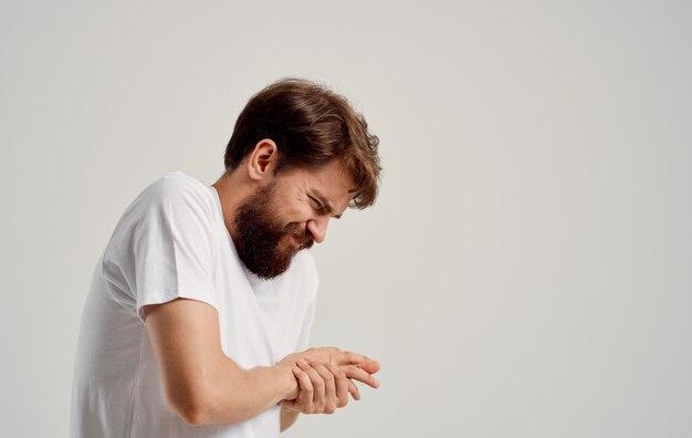 Мужчина испытывает боль и трогает рукой свет