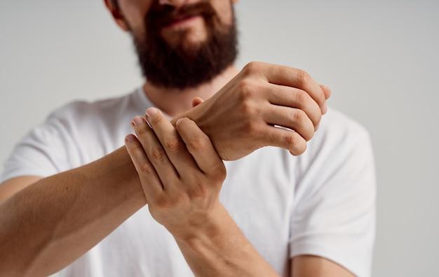 한 남자가 고통스럽고 손을 만진다.