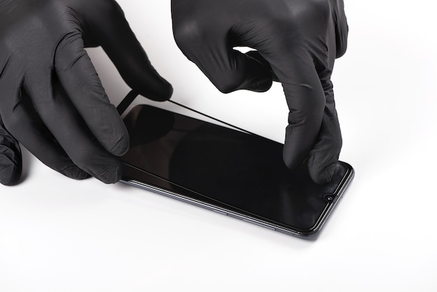 Мужчина устанавливает защитное стекло на экран смартфона.