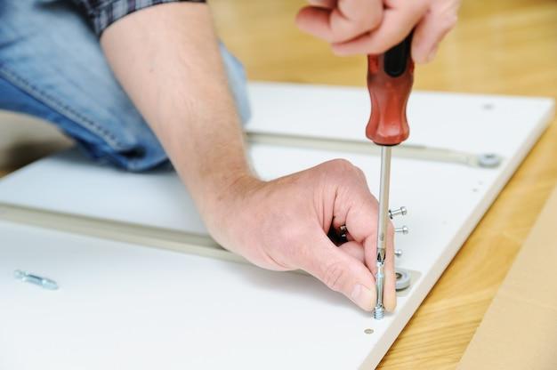Мужчина устанавливает соединительные болты на мебельном щите.