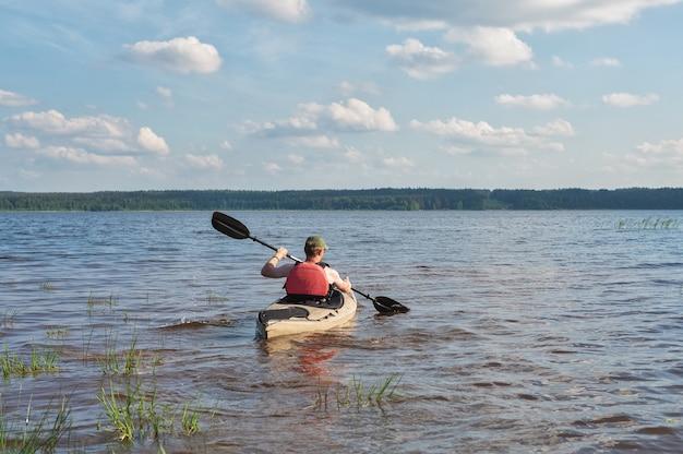 Мужчина каяется по реке в яркий солнечный день