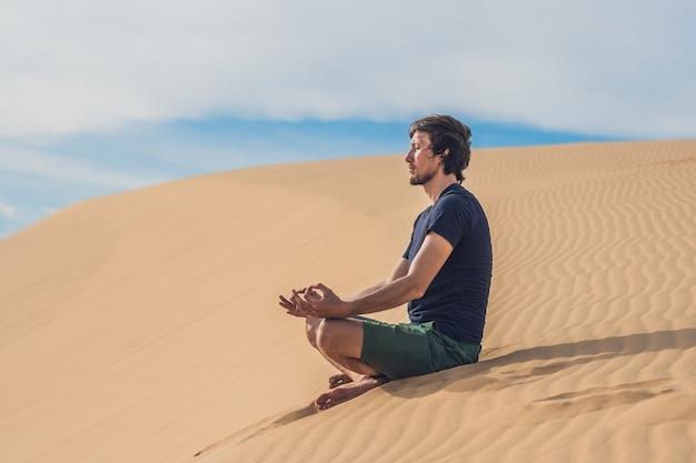 Мужчина медитирует на песке в пустыне.