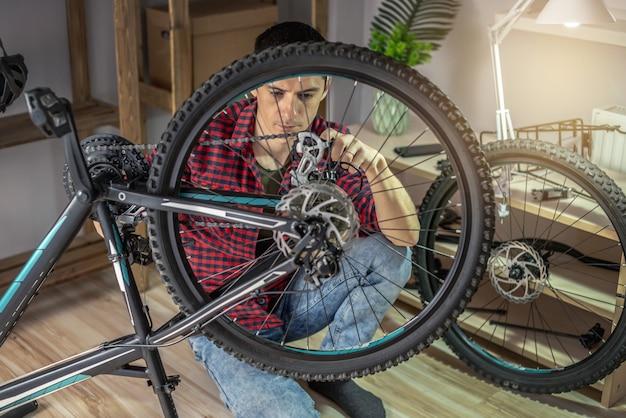 한 남자가 산악 자전거에서 유지 보수를 수행하고 있습니다. 새 시즌을 위한 자전거 고정 및 준비의 개념