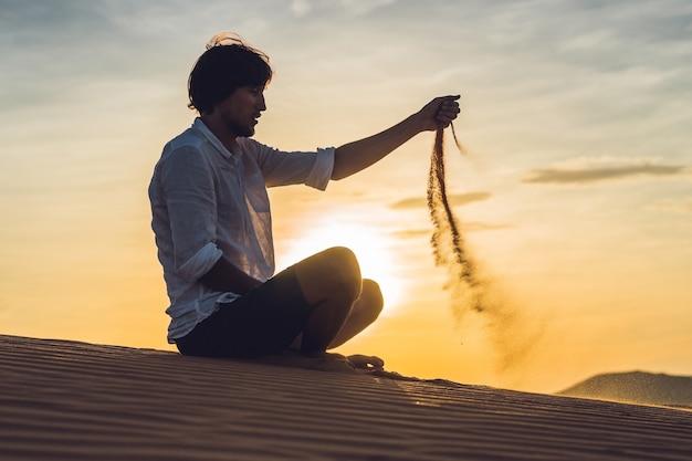 男が砂漠に砂を注いでいます。コンセプトの指を介して砂。