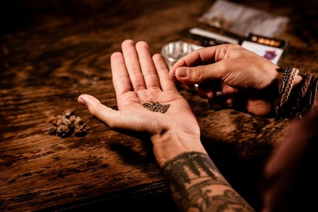 Мужчина готовит косяк, измельчая почки марихуаны в руках.