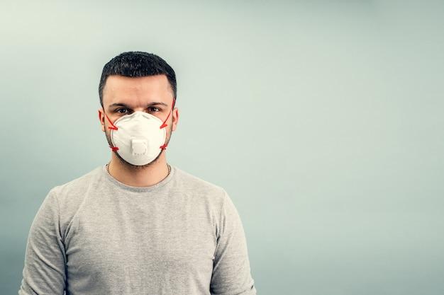 男が防護マスクをつけています。コロナウイルスからの呼吸保護。ウイルス感染のパンデミックに対する個人用保護具。 covid19。
