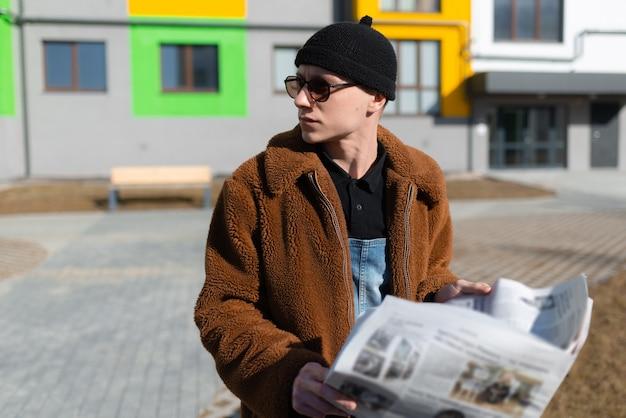 男が通りの新聞でニュースを読んでいる